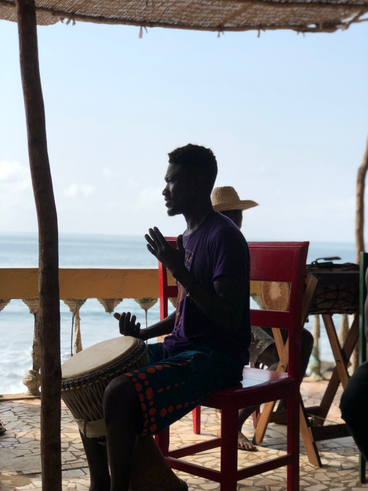 silhouette photo of Namory with a djembe and ocean in background